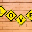 Love sign on brick wall — Stock Photo