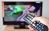 Mano señalando un control remoto de tv para la televisión — Foto de Stock