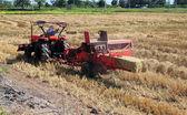 Granjero y tractor de embalaje de paja en el campo en Tailandia — Foto de Stock