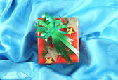 Red gift box with green ribbon on blue satin — Stock Photo