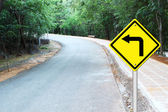 Turn left warning sign on curve road — Stock Photo