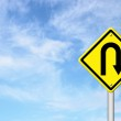Yellow warning sign u-turn roadsign with blue sky background — Stock Photo
