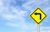 Road Sign - Left Turn Warning with blue sky — Stock Photo