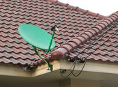 Satellite dish on the roof of tile — Stock Photo