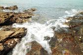 Meereswellen schlagen runde felsen und plantschen — Stockfoto