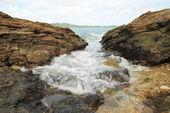 Sea waves hitting round rocks and splashing — Stock Photo