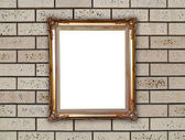 Golden frame on brick stone wall  — Stock Photo