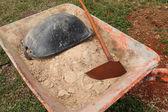 Old wheelbarrow with sand and equipment — Stock Photo