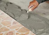 Handyman laying tile, trowel with mortar — Stock Photo