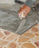 Handyman laying tile, trowel with mortar — Stock Photo