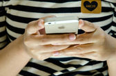 Girl hand holding and using an iPhone 5s — Stock Photo