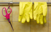 Rubber Gloves and Scissors Against Kitchen's Wall — Stock Photo