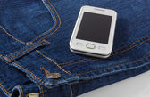 Mobile Phone on Blue Jeans — Stock Photo