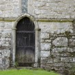 An old wooden door, in the stone wall of an old 14th Century church — Stock Photo