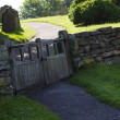 Old wooden double gate in dry stone wall to churchyard - Stock Photo