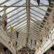 Colourful bunting flags in a glass rooved walkway in an English town — Stock Photo