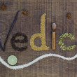 The word Vedic spelled out in ayurveda spices and seeds on a wooden board - Stock Photo