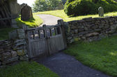 Old wooden double gate in dry stone wall to churchyard — Stock Photo