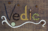 The word Vedic spelled out in ayurveda spices and seeds on a wooden board — Stock Photo
