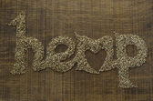 The word Hemp written artistically in hemp seeds on a wooden chopping board — Stock Photo