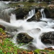 Pebbles or rocks in creek or stream flowing water — Stockfoto