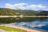 Reflection in smooth water of mountain lakes — Stock Photo