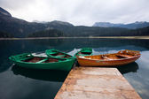 Smooth water of mountain lakes and boats — Stock Photo