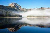 Lago de montaña brumosa con cielo azul — Foto de Stock