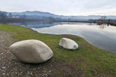 Rocks on the shore of the lake. house in the distance — Stock Photo