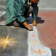 Artist paints with colorful chalks on the street image of saints — Stock Photo