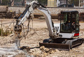 Excavator with hammer engaged in excavation of foundation — Stock Photo