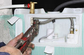 Worker assembles a manifold water system with focus on hands or tool — Stockfoto