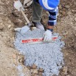 Worker puts plan a level to the foundation of the sidewalk — Stock Photo #47713295