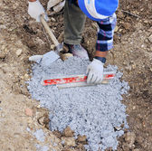 Worker puts plan a level to the foundation of the sidewalk — Stock Photo