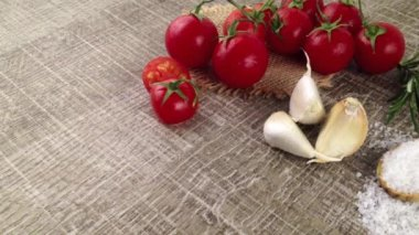 Closeup of bunch of wet tomatoes, garlics and scoop with salt on wooden kitchen table — Stock Video