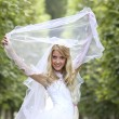 Happy bride in park — Stock Photo