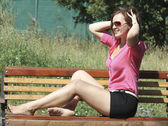 Young woman sitting on bench — Stock Photo