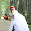 Crazy bride with chainsaw in park — Stock Photo