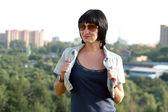 Glad brunett kvinna i jeansjacka — Stockfoto