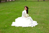 Happy bride sitting on grass — Stock Photo