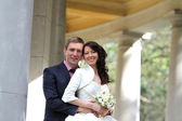 Happy bride and groom near columns — Stock Photo