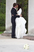 Bride and groom kissing near columns in park — Stock Photo