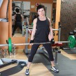 Young woman with barbell — Stockfoto
