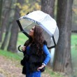 Stock Photo: Brunette womwith umbrellwalking in park