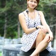 Woman sitting on old tires - Stock Photo