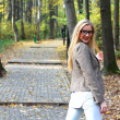 Stock Photo: Young woman walking in autumn park