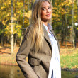 Pretty blonde woman in autumn park — Stock Photo