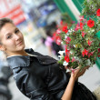 Brunette young woman with flowers — Stock Photo