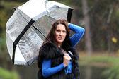 Brunette woman with umbrella in autumn park — Stock Photo