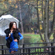 Woman with umbrella walking in park — Stock Photo